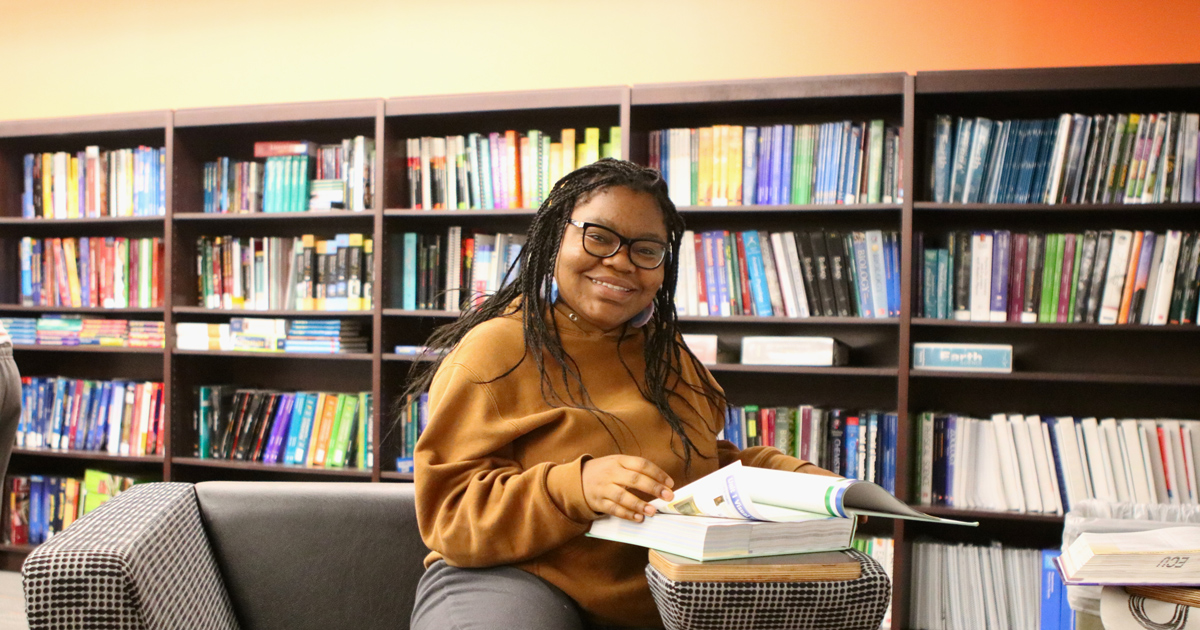 Education student sitting in library reading a book