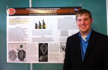 Josh Belcher of Ada stands at the national Beta Beta Beta convention in San Juan, Puerto Rico, with a poster detailing the nationally recognized research