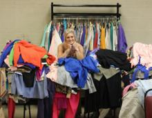 ECU business student Emilia Smith poses behind a pile of recently donated designer clothes.
