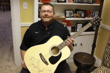 Coach McCarty with a guitar signed by Blake Shelton and Miranda Lambert