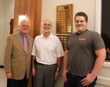 Stephen Decker (right), a student at East Central University, stands by the plaque that includes his name as the 2012 winner of ECU's prestigious Adolph Linscheid Award for speech and debate students.
