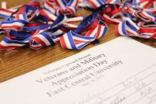 photo from the 2012 Veterans, Military Appreciation Day, hosted by East Central University's Veterans Upward Bound Program. In the photo is the registration sheet along with red, white and blue ribbons.