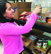 Student stocks shelves at ECU food pantry.