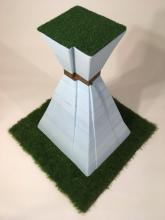 "This is a photograph of Leticia Bajuyo's creation ""Tighten Your Belt: Ranch"" made of cast iron, Styrofoam, artificial grass, steel and adhesive."
