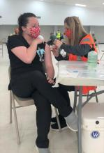 ECU Nursing professor Dr. Liz Massey, right, administers a vaccination to Nursing student Megan Jernigen in advance of opening the Pontotoc County Agri-Plex for public vaccinations.
